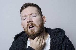 喉をおさえる男性